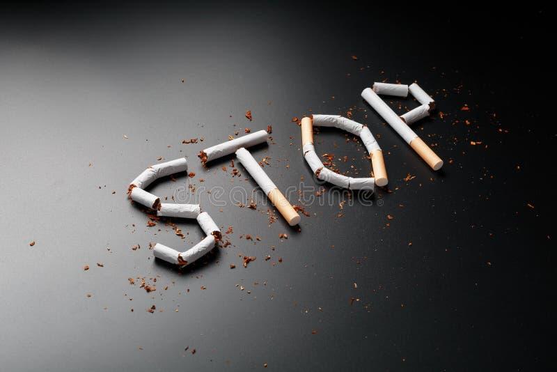 L'ARR?T d'inscription des cigarettes sur un fond noir Cessez le fumage Le concept des mises ? mort de tabagisme Inscription de mo images stock