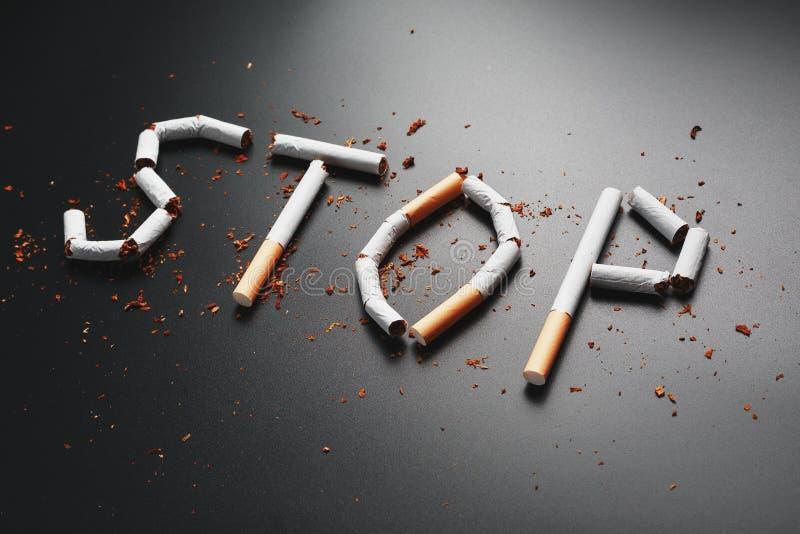 L'ARR?T d'inscription des cigarettes sur un fond noir Cessez le fumage Le concept des mises ? mort de tabagisme Inscription de mo photo stock