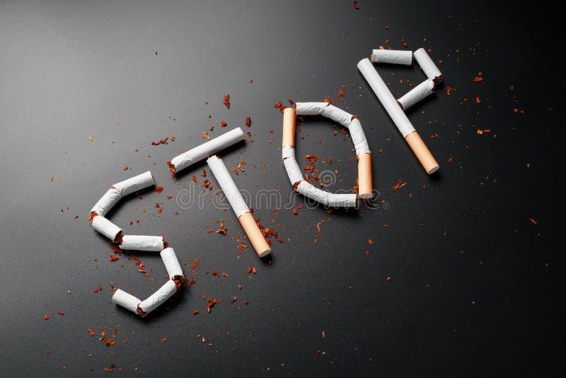 L'ARR?T d'inscription des cigarettes sur un fond noir Cessez le fumage Le concept des mises ? mort de tabagisme Inscription de mo photos libres de droits