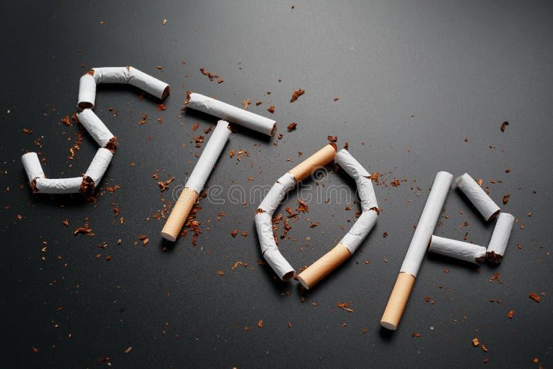 L'ARR?T d'inscription des cigarettes sur un fond noir Cessez le fumage Le concept des mises ? mort de tabagisme Inscription de mo photo libre de droits