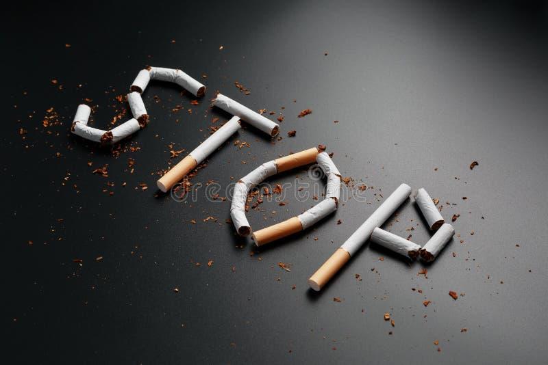 L'ARR?T d'inscription des cigarettes sur un fond noir Cessez le fumage Le concept des mises ? mort de tabagisme Inscription de mo photographie stock libre de droits