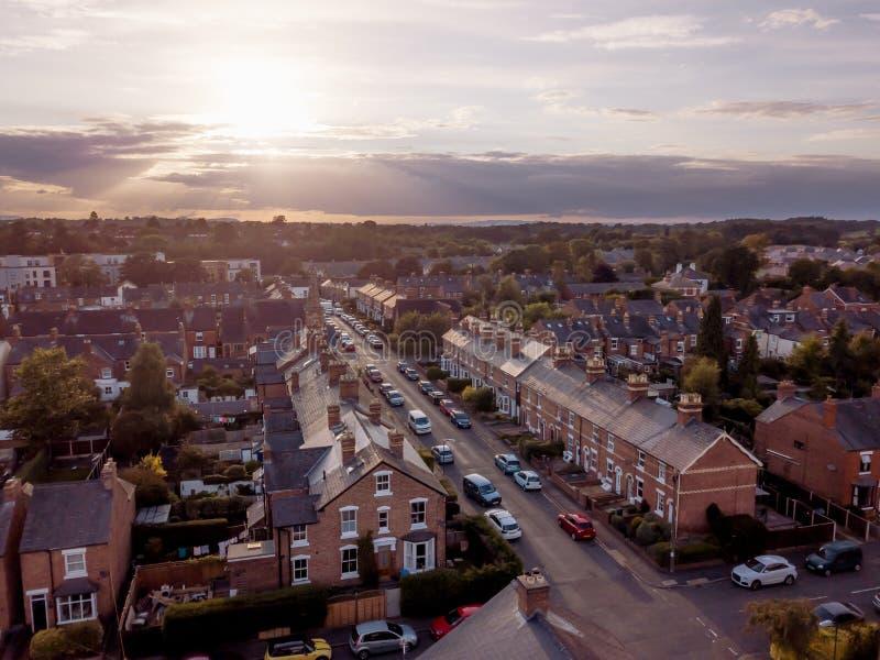 L'arrangement de Sun avec l'effet atmosph?rique au-dessus des maisons britanniques traditionnelles et l'arbre a ray? des rues photographie stock