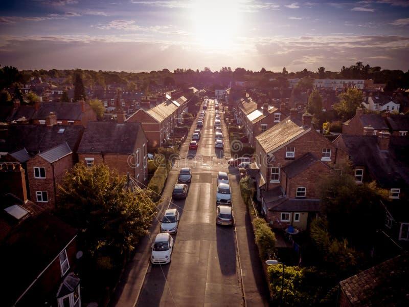 L'arrangement de Sun avec l'effet atmosph?rique au-dessus des maisons britanniques traditionnelles et l'arbre a ray? des rues images stock