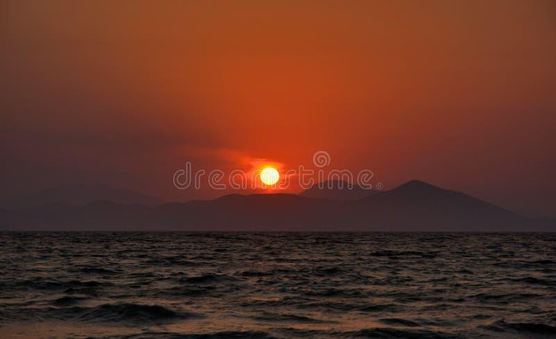 L'arrangement du soleil derrière les montagnes photos stock