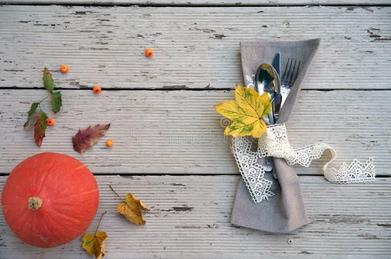 L'arrangement saisonnier de table d'automne avec le petit potiron et la chute laisse des baies sur des couleurs oranges et jaunes photographie stock libre de droits