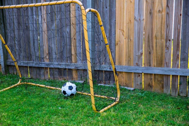 L'arrière-cour chldren le football à la barrière en bois avec le mur images stock
