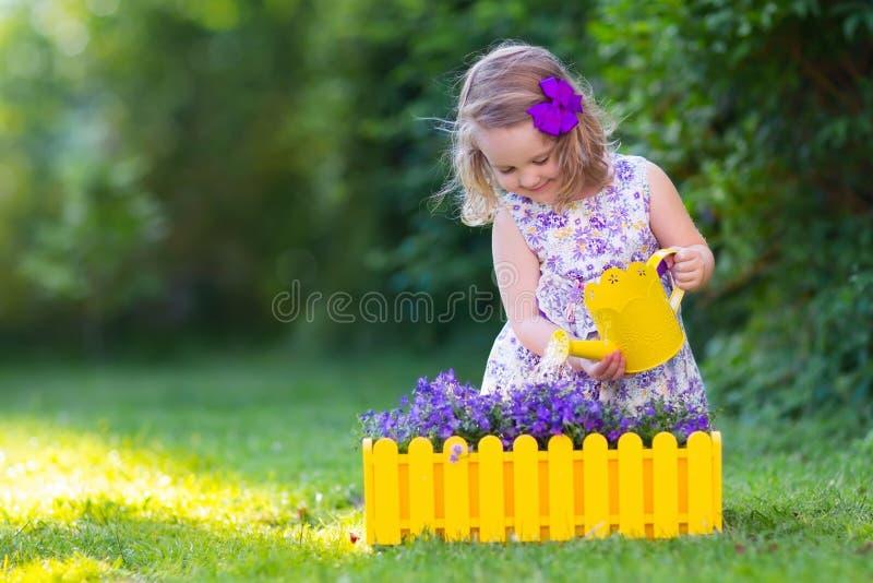 L'arrosage de petite fille farden des fleurs photographie stock