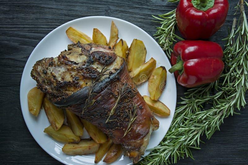 L'articolazione fritta della carne di maiale con le patate ? servito su un piatto bianco Ha decorato con pepe bulgaro fresco, ros immagine stock libera da diritti