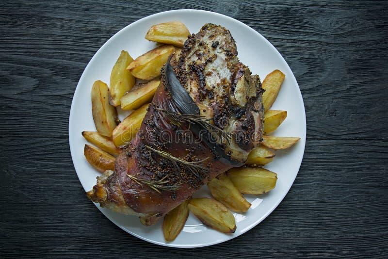L'articulation frite de porc a servi avec des pommes de terre servies d'un plat blanc Fond en bois fonc? Vue de ci-avant images libres de droits