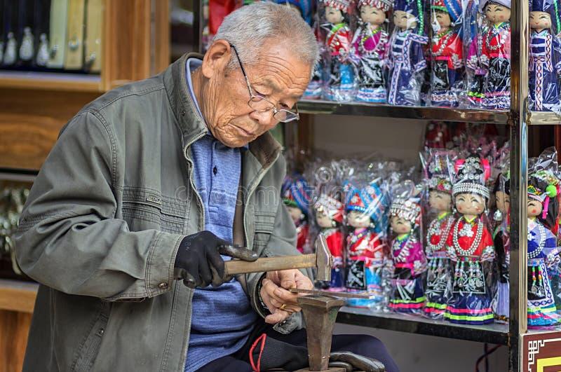 L'artigiano anziano che elabora l'argenteria