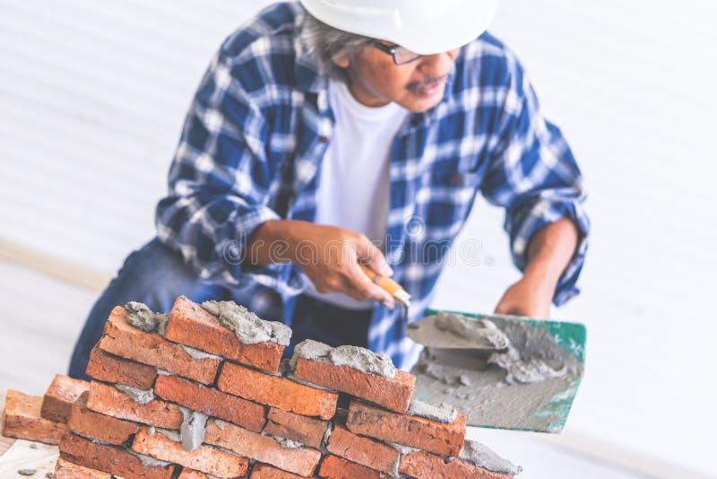 L'artigiano anziano del costruttore sta livellando il muro di mattoni fotografie stock
