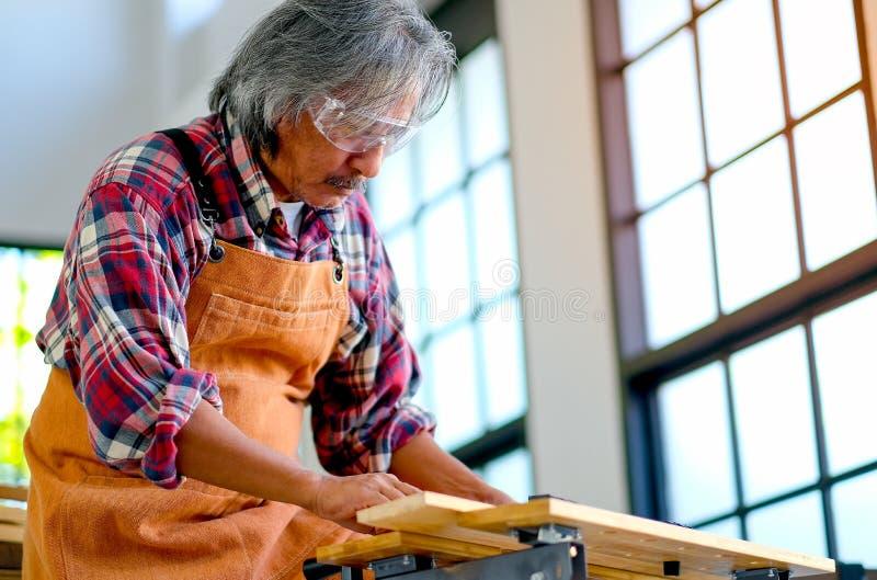L'artigiano asiatico anziano sta lavorando con i prodotti del legno nella stanza con la luce del giorno fotografia stock libera da diritti