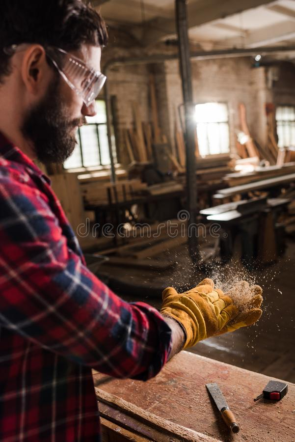 l'artigiano barbuto in protettivo googla e guanti che scuote i chip di legno dalle mani immagini stock libere da diritti