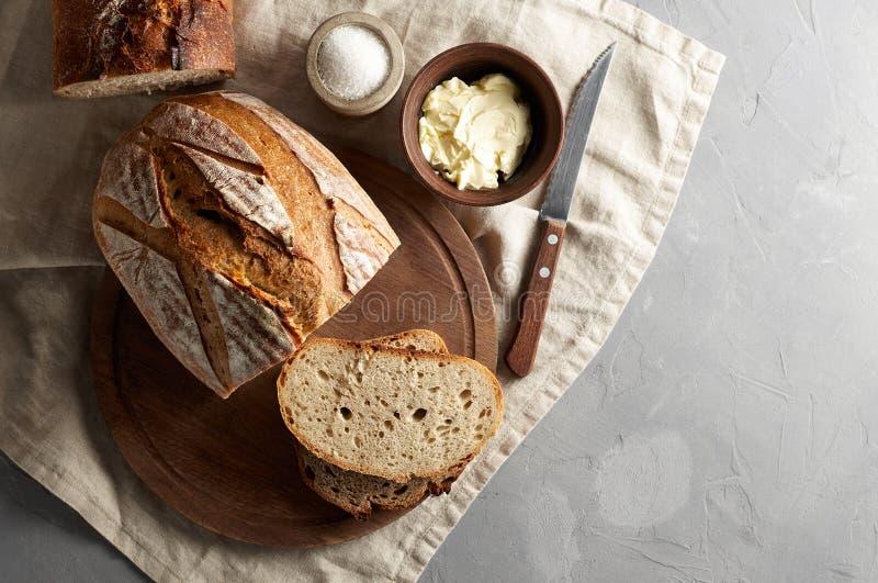 L'artigiano ha affettato il pane del pane tostato con burro e lo zucchero sul tagliere di legno Prima colazione semplice su fondo fotografia stock