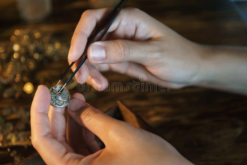 L'artigiano smantella l'orologio ed ottiene gli ingranaggi fotografia stock