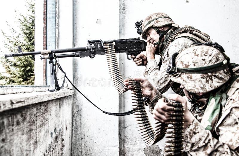 L'artilleur de machine d'armée attaque l'ennemi avec le feu visé photo stock