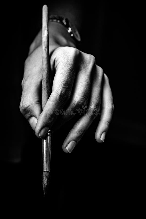 L'artist& x27 ; les mains de s tiennent une brosse photo stock