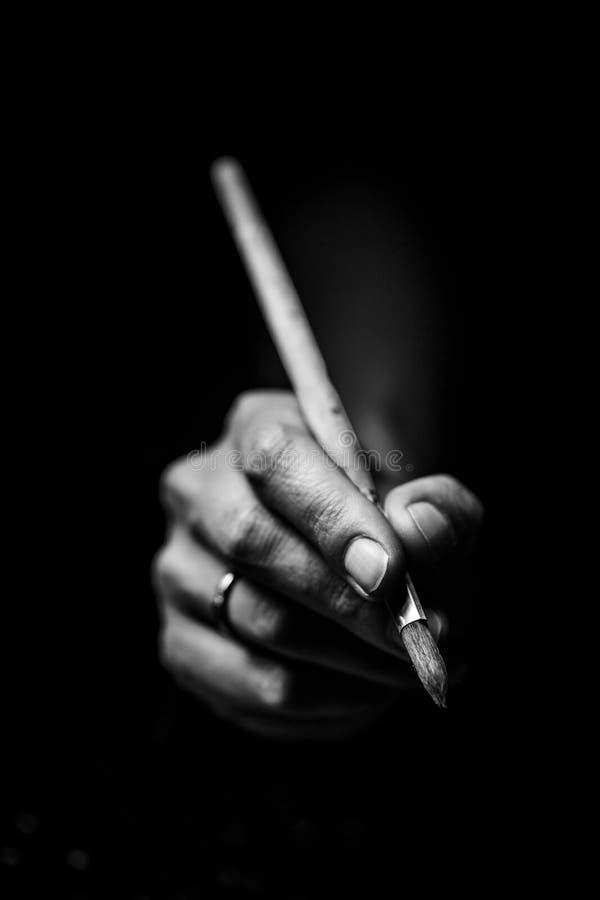 L'artist& x27 ; les mains de s tiennent une brosse photographie stock