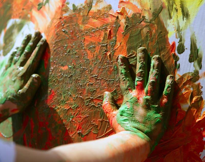 L'artista dei bambini passa a pittura i multi colori immagine stock