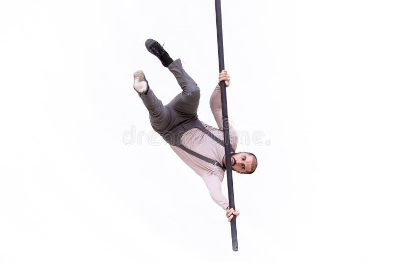 L'artista dell'acrobata ha appeso sottosopra durante la sua prestazione sul ballo del palo fotografia stock