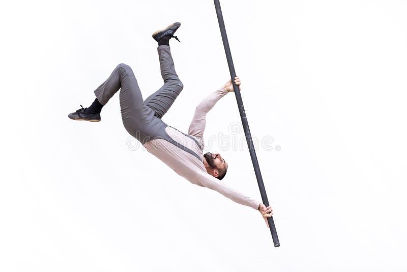 L'artista dell'acrobata ha appeso sottosopra durante la sua prestazione sul ballo del palo immagine stock libera da diritti