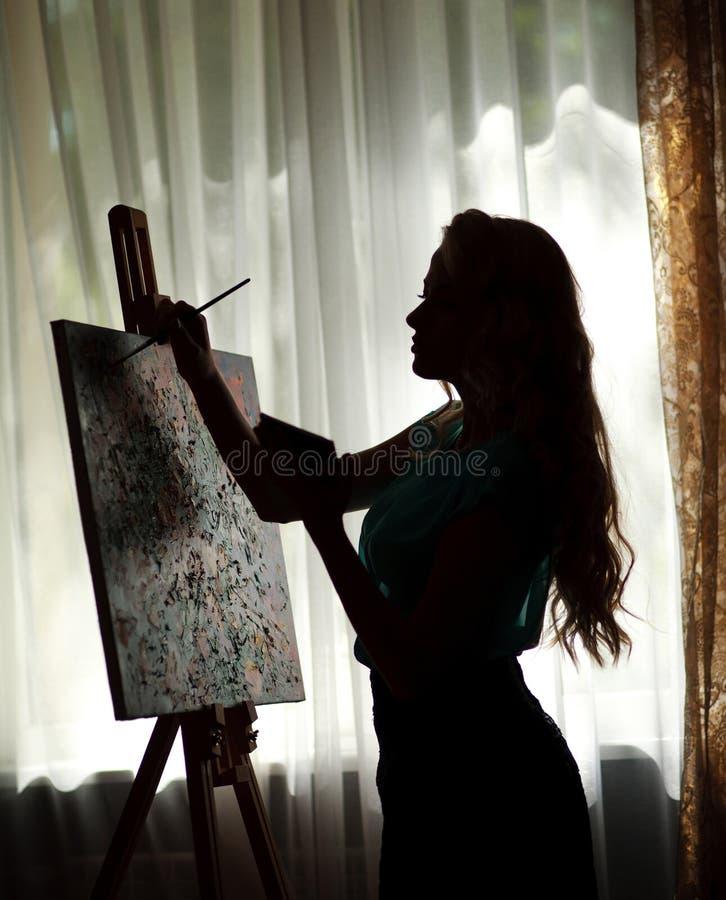 L'artista della donna della siluetta disegna l'immagine della pittura sul cavalletto fotografia stock
