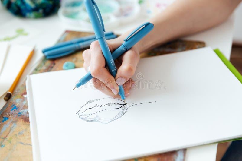 L'artista della donna passa il disegno con la penna del gel in sketchbook immagine stock libera da diritti