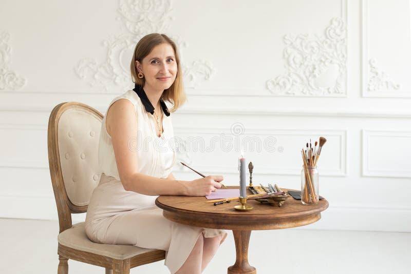 L'artista della ragazza è ispirato e dipinge un'immagine Tenute una spazzola Fuoco molle L'officina dell'artista interno immagini stock libere da diritti