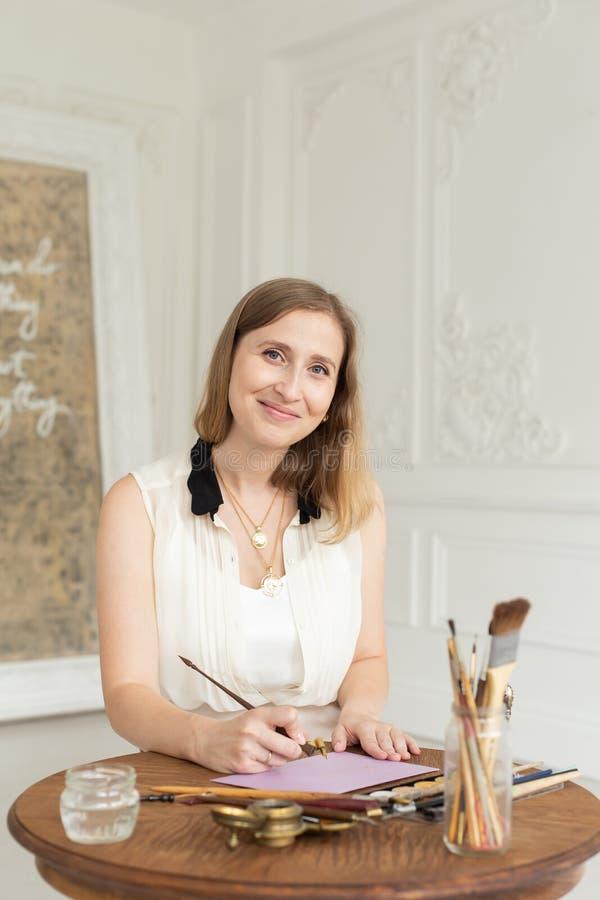 L'artista della ragazza è ispirato e dipinge un'immagine Tenute una spazzola Fuoco molle L'officina dell'artista interno fotografie stock libere da diritti