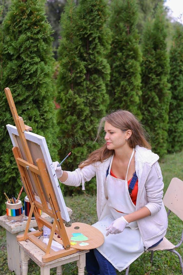 L'artista della ragazza dipinge l'immagine e si siede sulla sedia sui lati del cavalletto della t fotografia stock libera da diritti