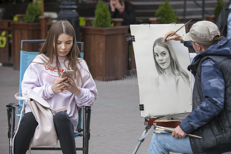 L'artista della via dipinge il ritratto di una ragazza sulle vie di Mosca fotografia stock