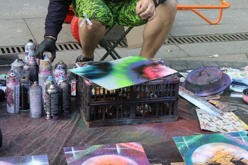 L'artista della via dipinge una latta di pittura su carta per i compratori immagine stock