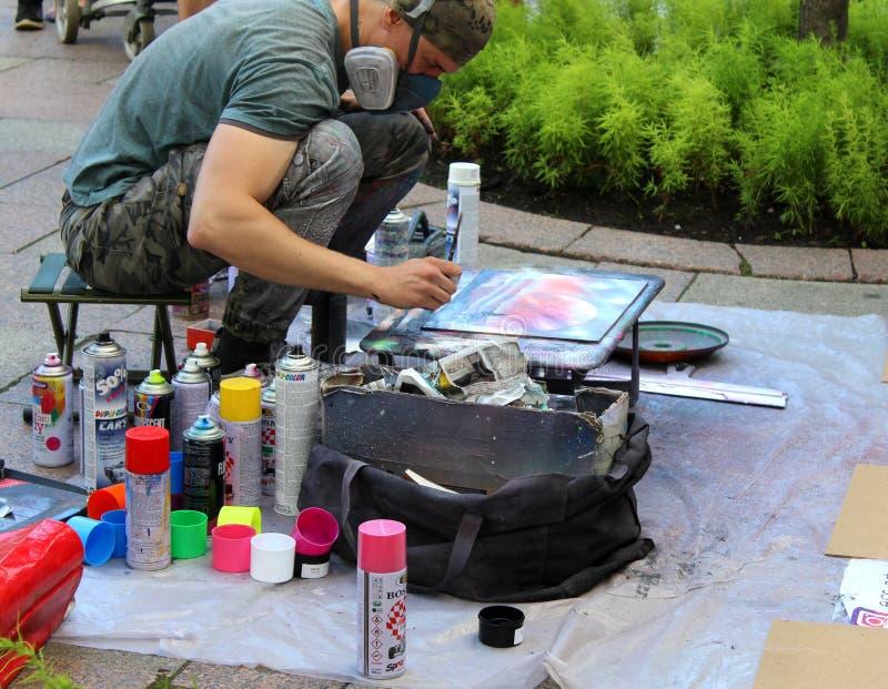 L'artista della via dipinge una latta di pittura su carta per i compratori fotografia stock libera da diritti