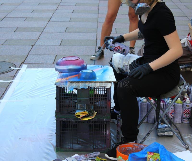 L'artista della via dipinge una latta di pittura su carta per i compratori immagini stock