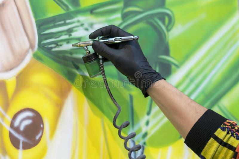L'artista dipinge un'immagine con una pistola a spruzzo fotografie stock