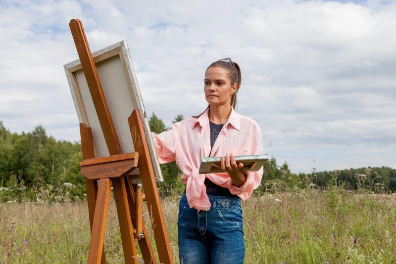 L'artista dipinge un'immagine nel campo fotografie stock libere da diritti