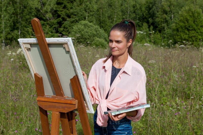L'artista dipinge un'immagine nel campo immagini stock libere da diritti