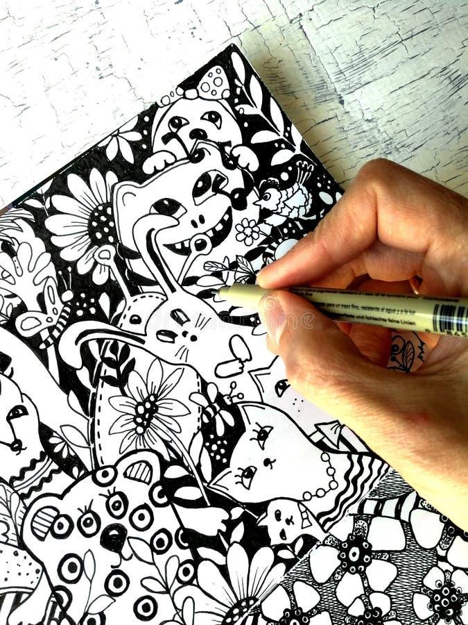 L'artista disegna gli animali svegli di kawaii nello stile grafico Mano e primo piano della fodera fotografie stock