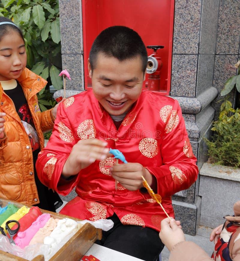 L'artista piega maschio fa la bambola della pasta del cinese tradizionale immagine stock libera da diritti