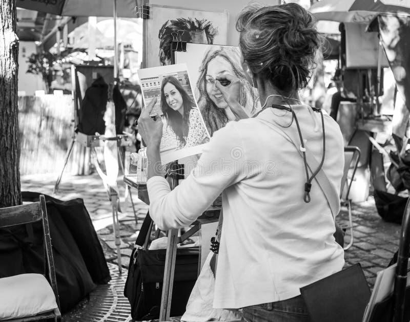 L'artista schizza il ritratto dalla fotografia, Place du Tertre, Montmartre, Parigi fotografia stock libera da diritti