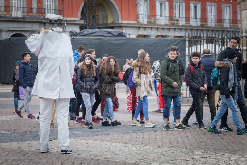 L'artista sta lavorando come statua viva dell'uomo senza testa in vestito bianco, immagini stock