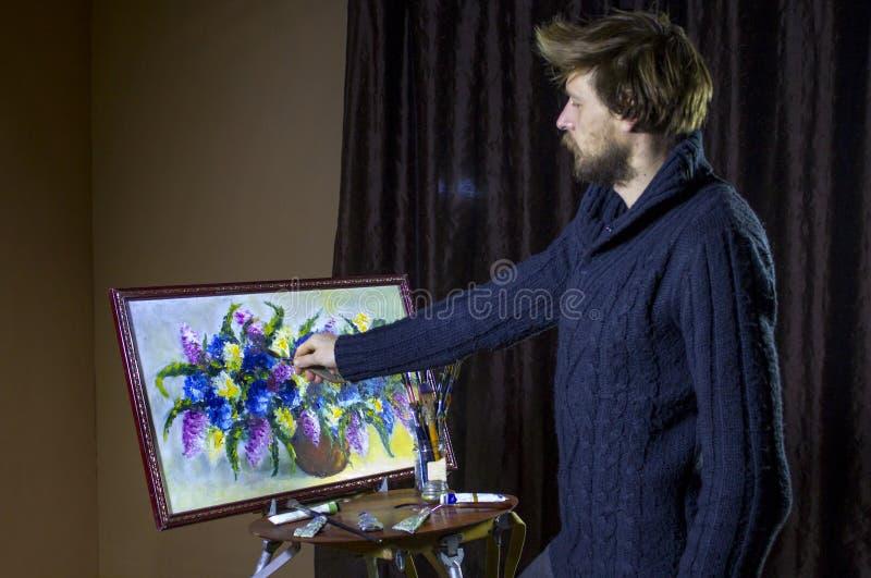 L'artiste barbu masculin dans un chandail foncé dessine toujours une vie artistique de fleurs de peinture de brosse dans le studi image stock