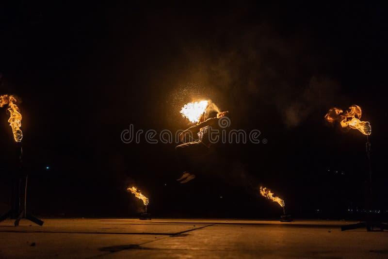 L'artiste d'exposition du feu respirent le feu dans l'obscurité image libre de droits