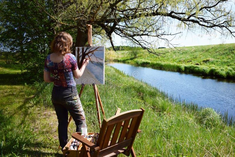L'artiste de femme peint la peinture de paysage de la petite rivière images stock