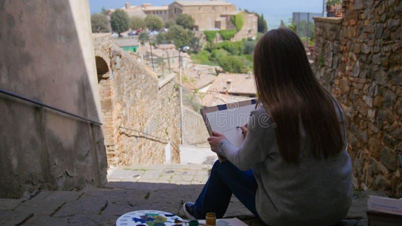 L'artiste de jeune femme s'asseyent sur les escaliers et dessinent l'image de la ville photo stock