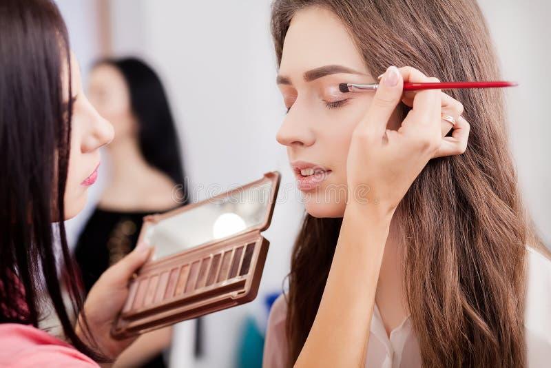 L'artiste de maquillage fait le maquillage à une belle fille dans un salon de beauté photos libres de droits