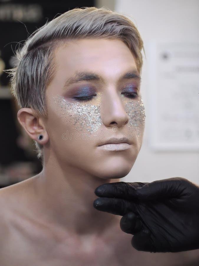 L'artiste de maquillage fait le maquillage au jeune modèle masculin comme César images stock