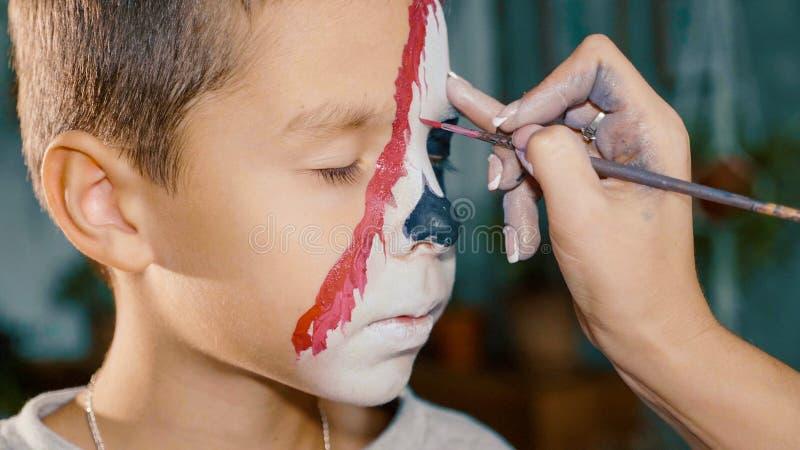 L'artiste de maquillage incite le garçon Halloween à composer Art de visage d'enfant de Halloween photos stock