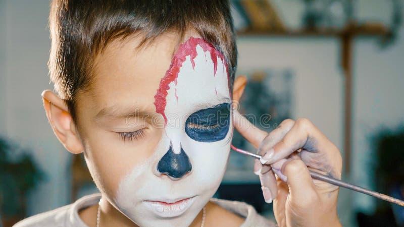 L'artiste de maquillage incite le garçon Halloween à composer Art de visage d'enfant de Halloween photographie stock libre de droits