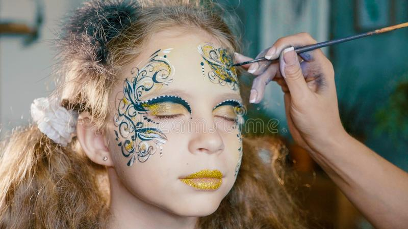 L'artiste de maquillage incitent la fille à faire face à l'art photographie stock